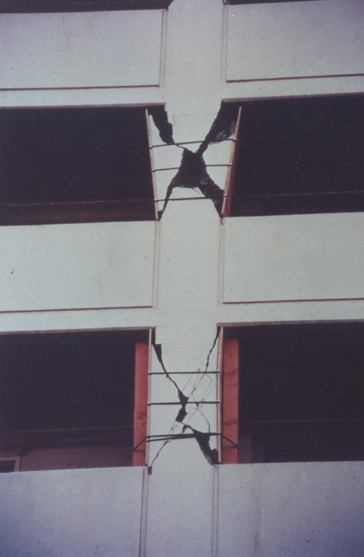 Balcony parapets induced short-column effects in the Champaign Tower moment frames. Typical X-shaped shear cracking from the short-column behavior is shown. [5]