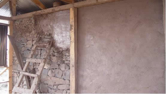 Plastering with cement sand plaster or mud mixed with natural fibres (note that the wall is not a Dhajji wall).