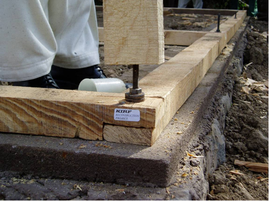 Bolting of plinth band with foundation. Note that a damp proof course has not been used.