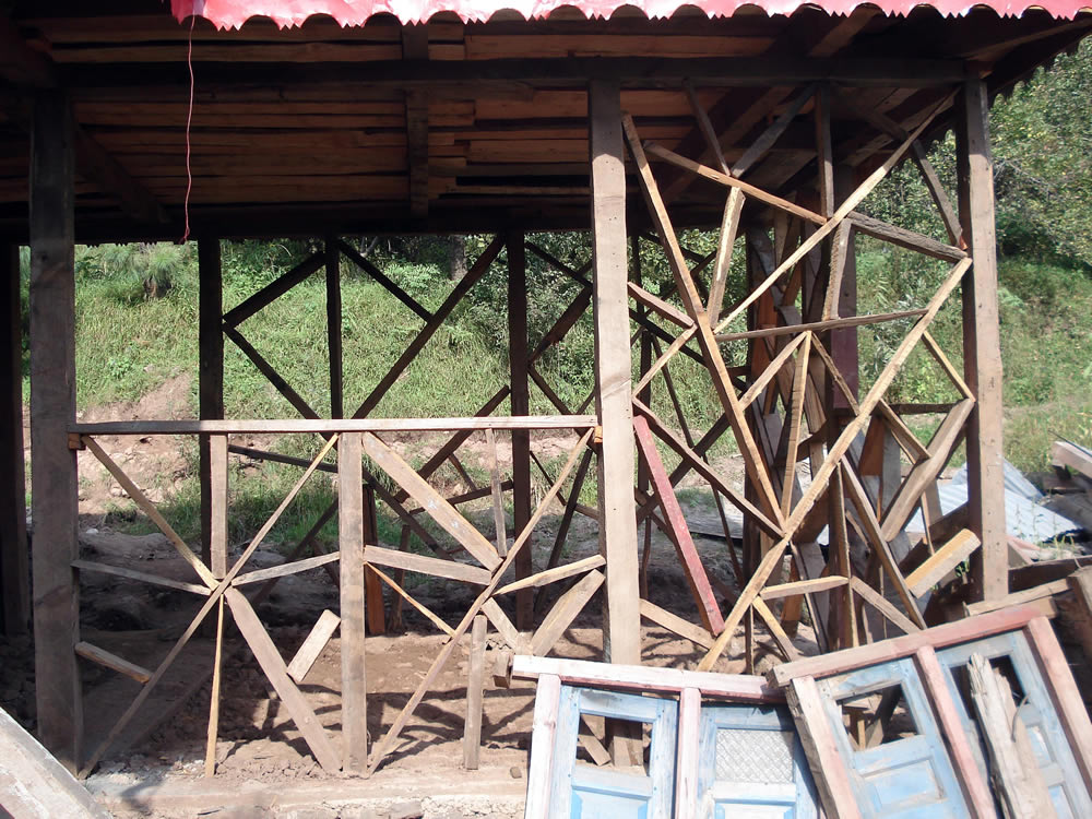 Mixed bracing pattern making uses of salvaged timber and window frames.