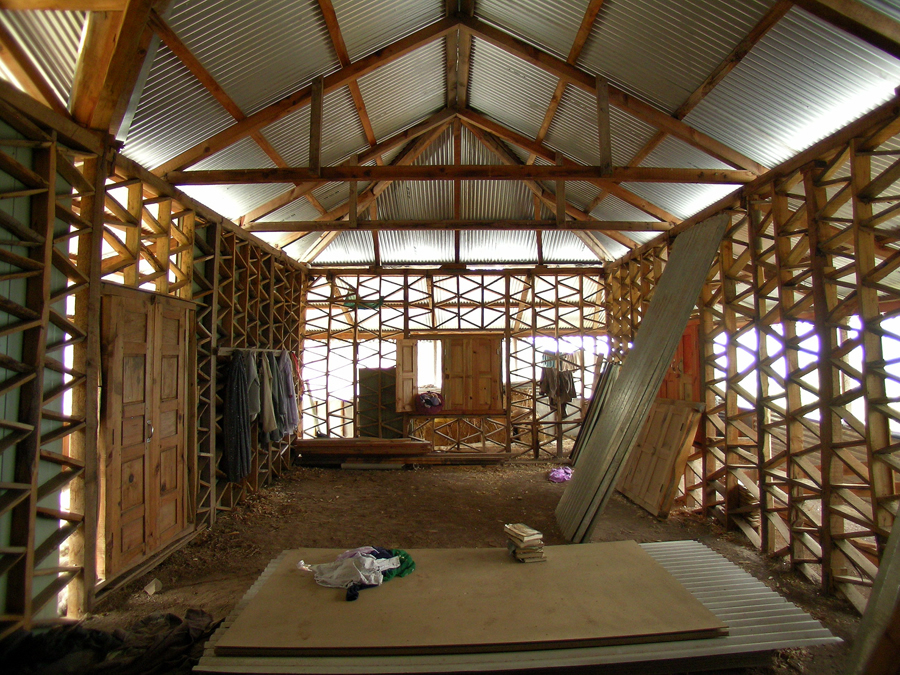 Inside view of a 1 storey house under construction. Note that the timber frame is in direct contact with the ground.