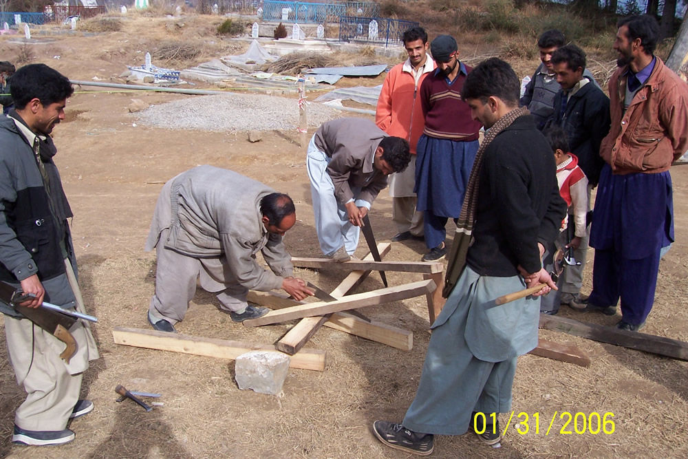 Cutting of timber sections. Note the child watching and learning