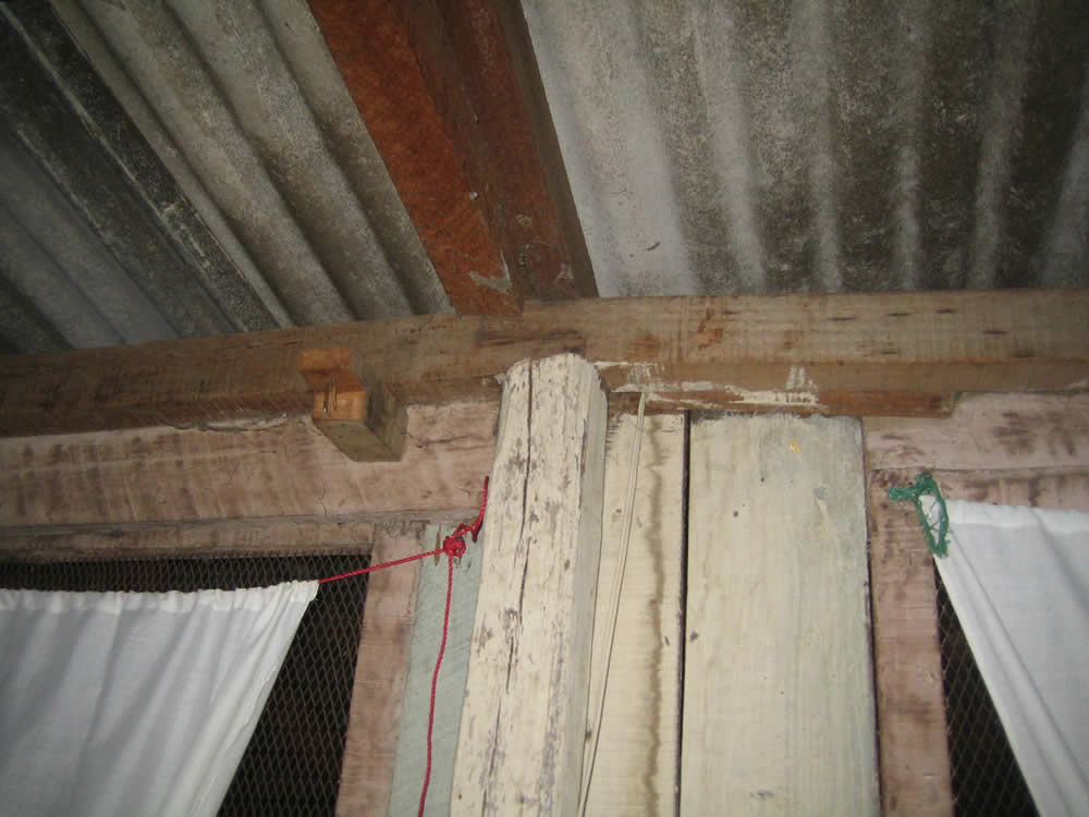 Roof made of asbestos sheets supported by wooden beams which loosely rest on the wooden walls.