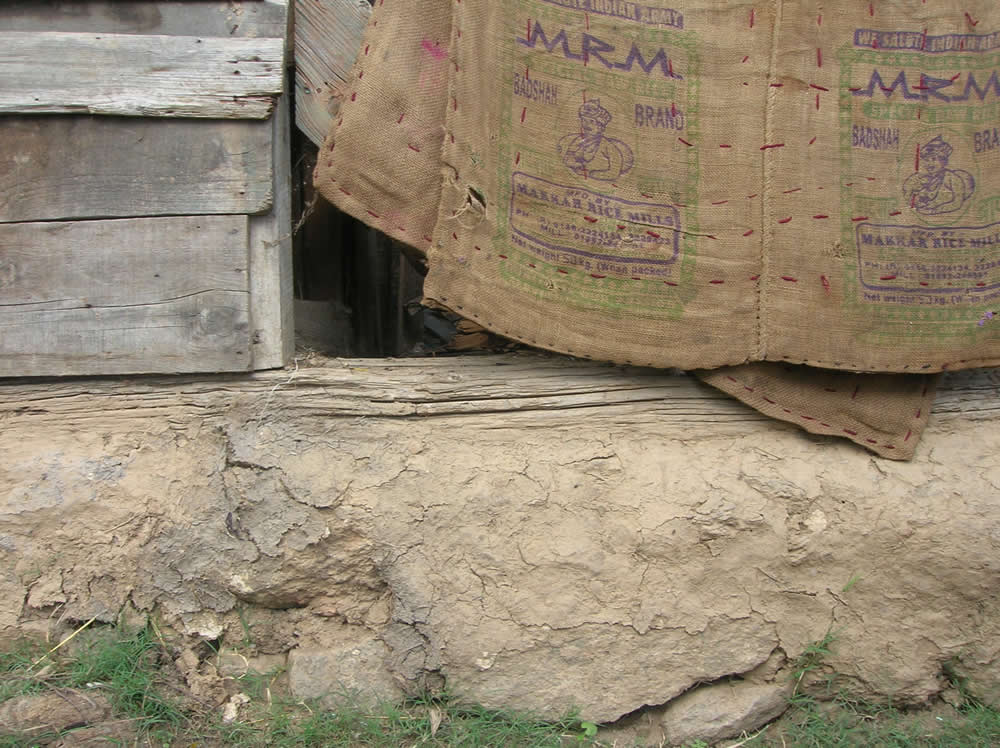Stone foundation rising above ground level, in a 